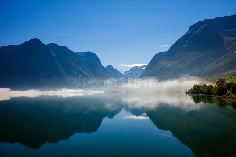 Фьорд в Норвегии при горы и туман вися над водой стоковое фото
