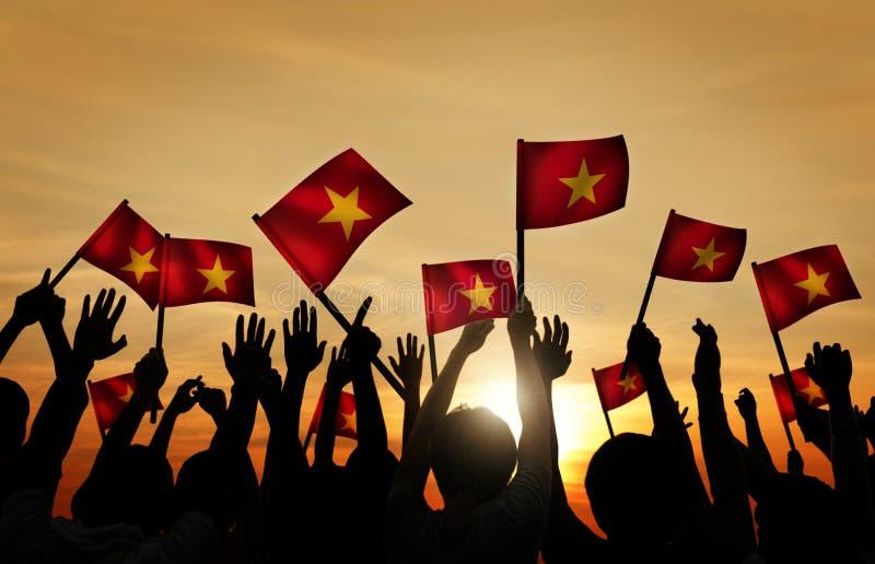 Флаги вьетнамца группы людей развевая в заднем Lit стоковое изображение
