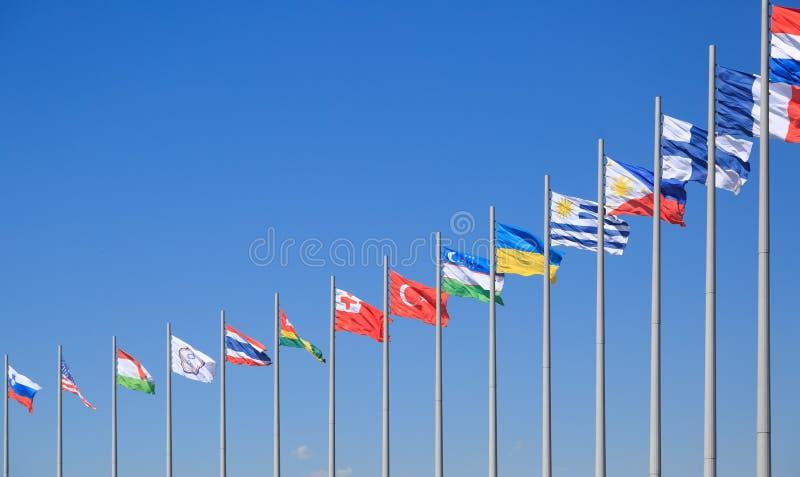 Флаги много стран порхают на предпосылке голубого неба в солнечном дне стоковое изображение