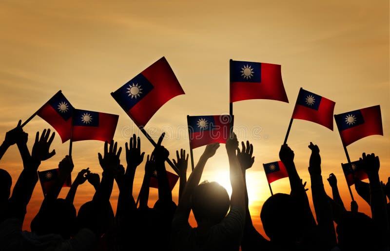 Флаги тайванца группы людей развевая в заднем Lit стоковое фото