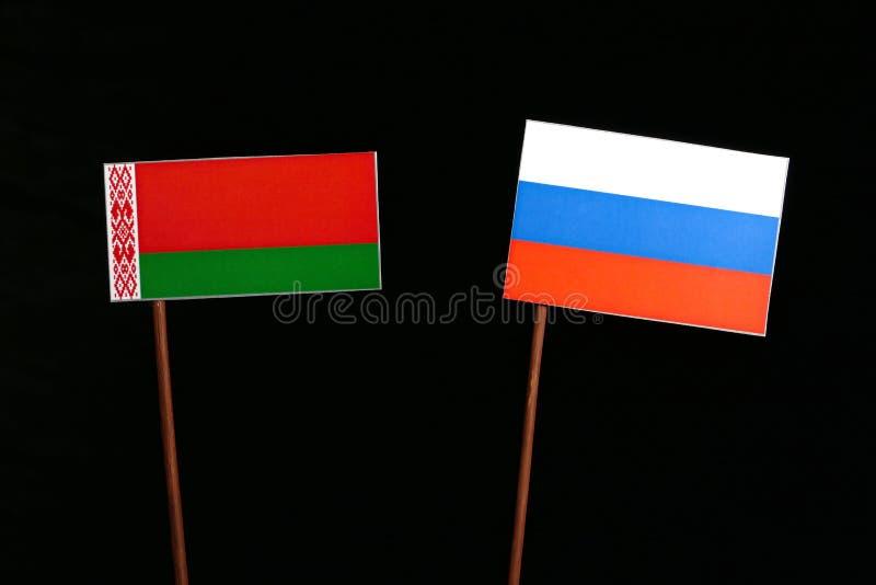 Флаг Беларуси при русский флаг изолированный на черноте стоковые изображения