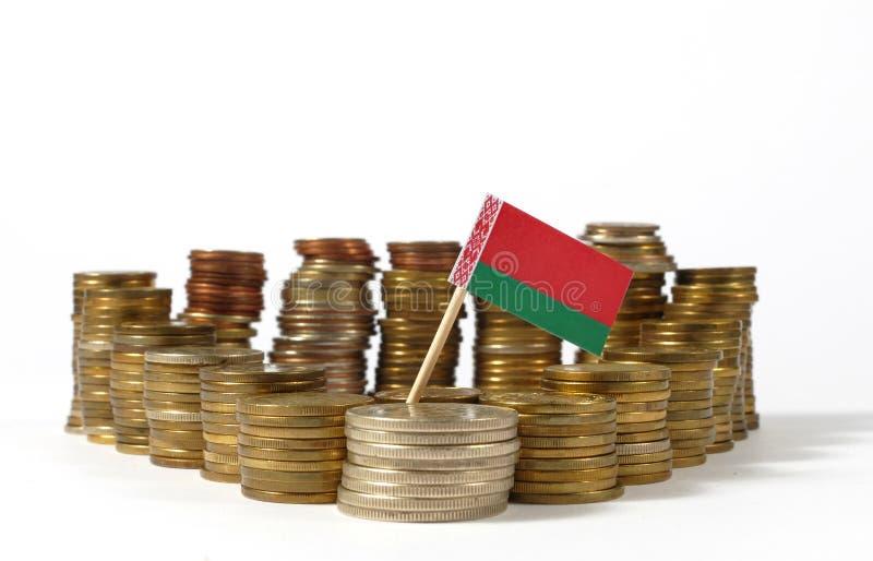 Флаг Беларуси с стогом монеток денег стоковое изображение rf