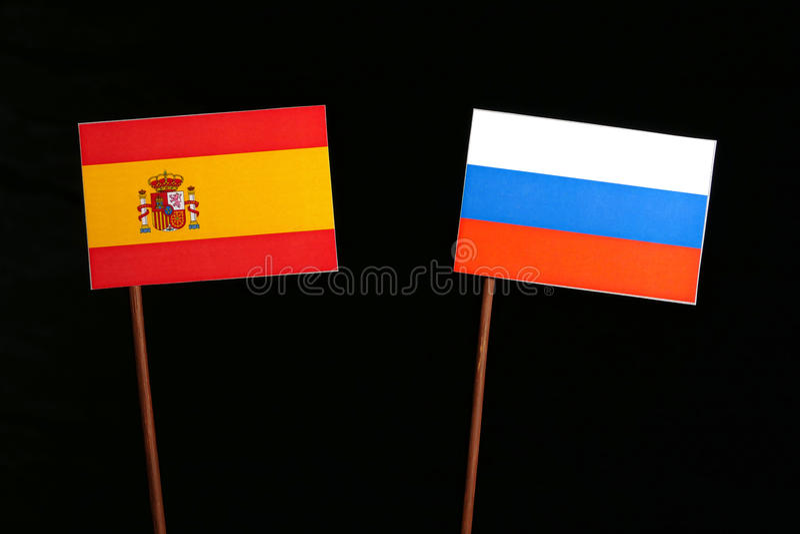 Флаг испанского языка с русским флагом на черноте стоковые фото