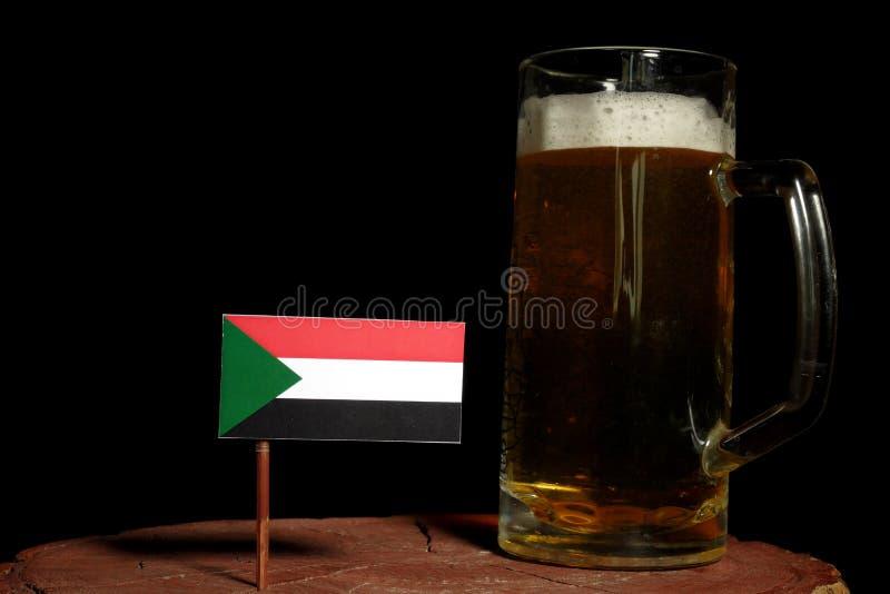 Флаг Судана с кружкой пива на черноте стоковые изображения rf