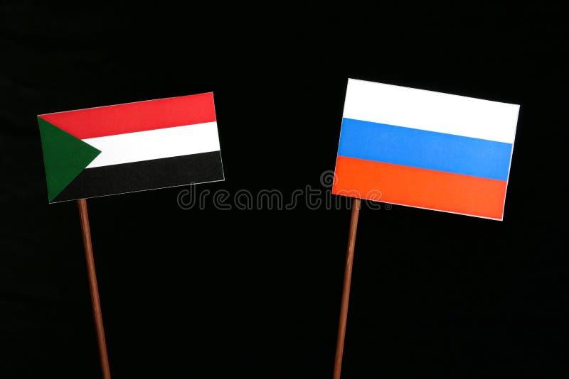 Флаг Судана с русским флагом на черноте стоковые изображения rf