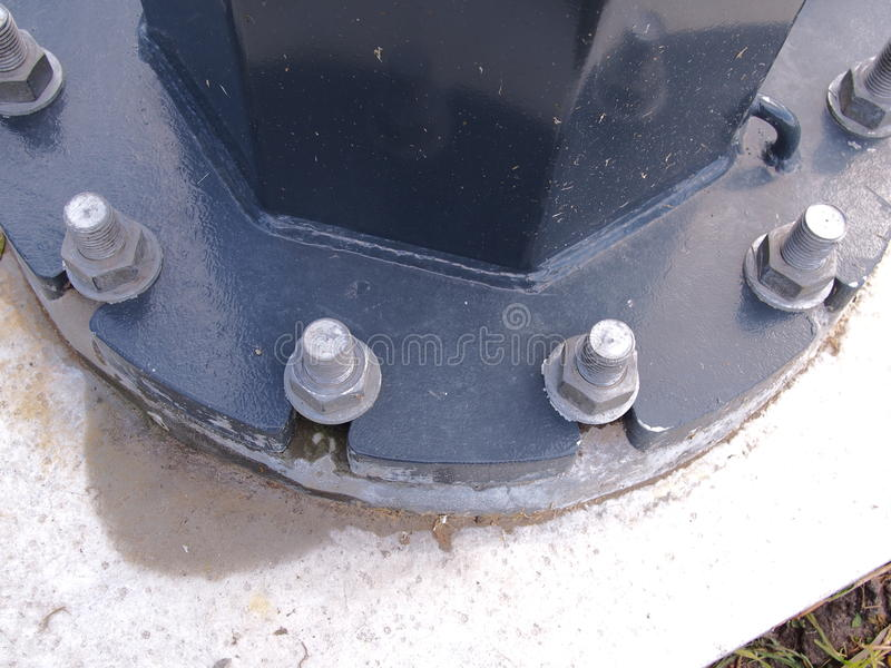 Фланец поляка с тяжелыми продетыми нитку гальванизированными стержнями и гайками на конкретной подбетонке стоковое фото rf