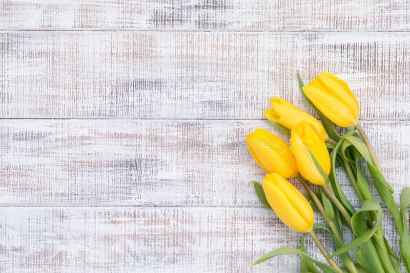 Флористическая карточка с желтыми тюльпанами над винтажной деревянной предпосылкой стоковая фотография