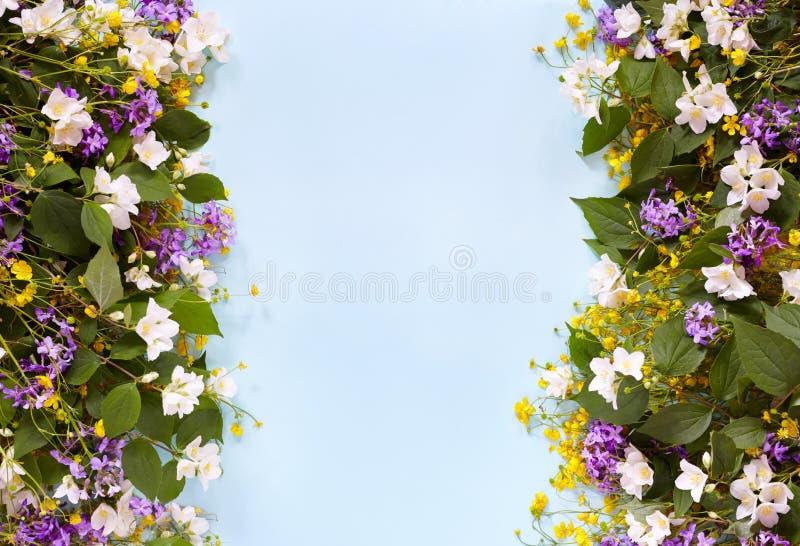 Флористическая предпосылка лета на голубой таблице с сиренью, желтыми wildflowers и жасмином над взглядом Настроение лета стоковое фото