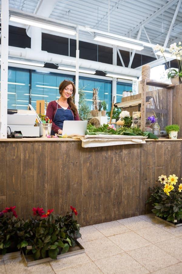 Флорист используя компьтер-книжку на счетчике в цветочном магазине стоковая фотография rf