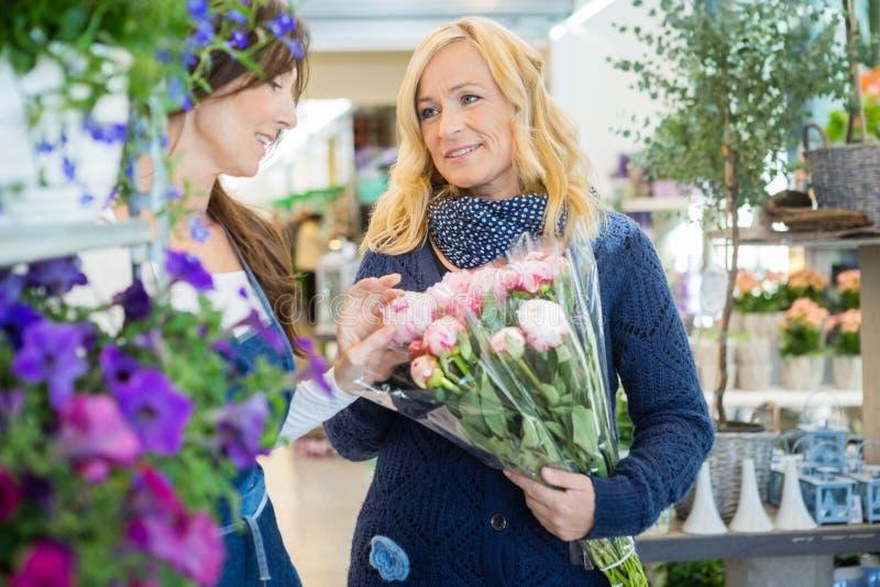 Флорист помогая клиенту в покупая цветке стоковое фото rf