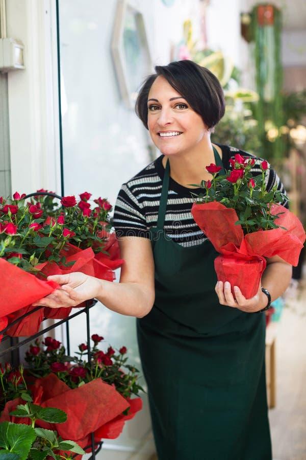 Флорист работая в флористическом магазине стоковое фото rf