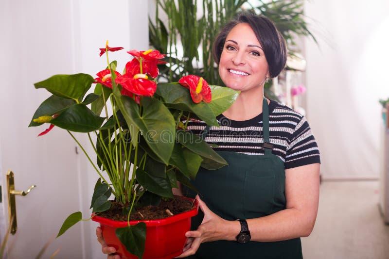 Флорист работая в флористическом магазине стоковое изображение