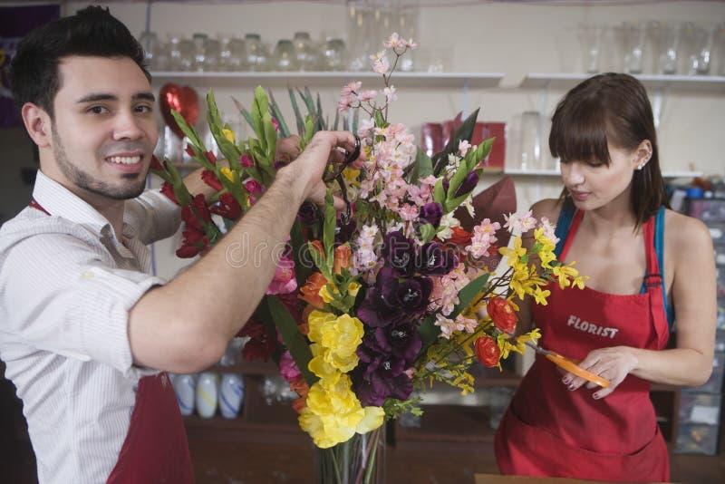 Флорист работая с коллегой в цветочном магазине стоковое фото rf