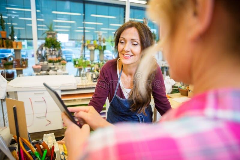Флорист смотря женского клиента используя цифров стоковая фотография