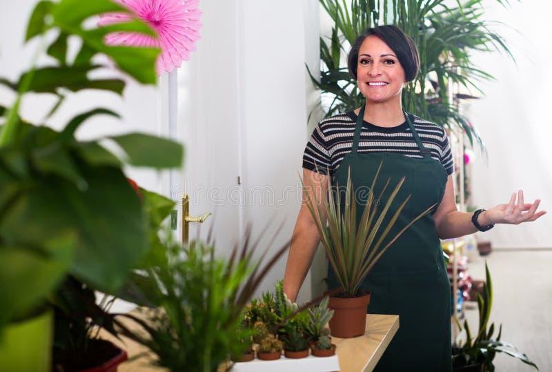 Флорист усмехаясь среди заводов стоковое фото