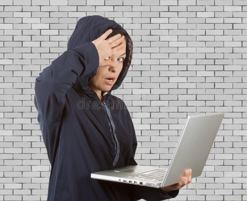 Хакера женщины Catched клобук уголовного нося на использовании компьтер-книжки стоковые фото
