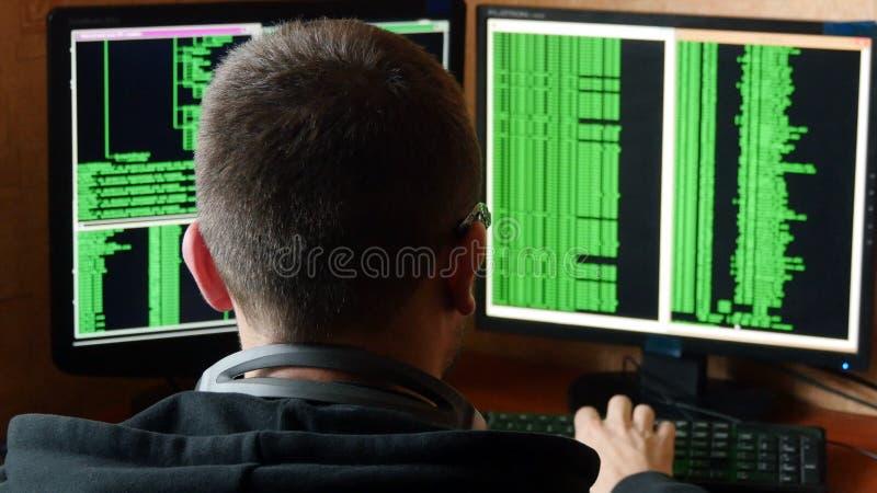 Хакер в стеклах ломая код Сеть уголовного хакера прозорливая от его темной комнаты хакера Компьутерная программа стоковое фото