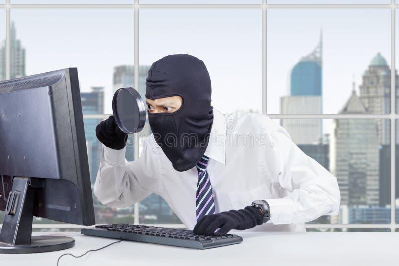 Хакер использует увеличитель и маску для того чтобы украсть данные стоковое фото