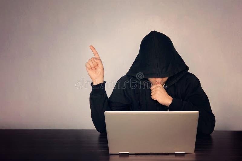 Хакер с капюшоном перед его пальцем компьютерной выставки темная сторона hooded концепция технологии, хакер указывает палец на пу стоковое фото rf