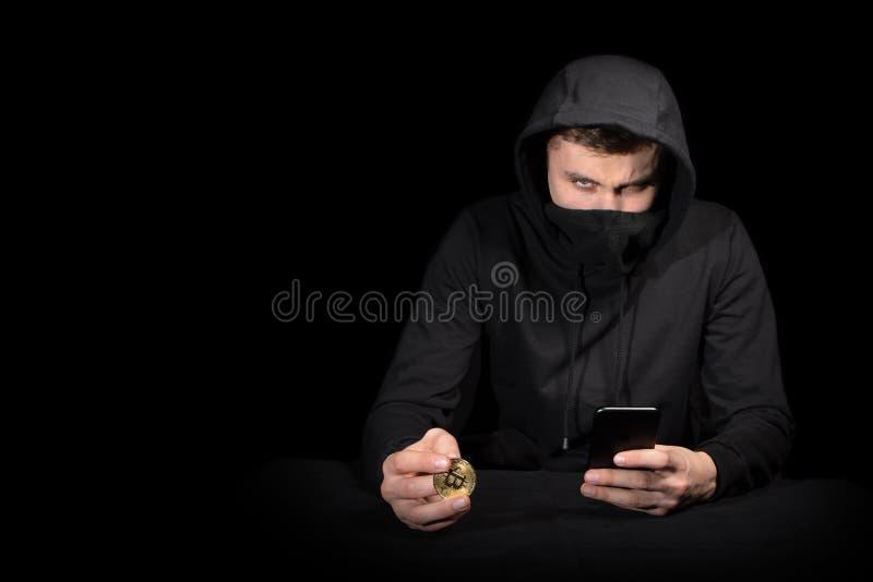 Хакер с мобильным телефоном и bitcoin начиная кибер атаку, на черноте стоковые изображения rf