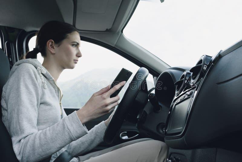 Халатная женщина используя смартфон в ее автомобиле стоковое изображение rf