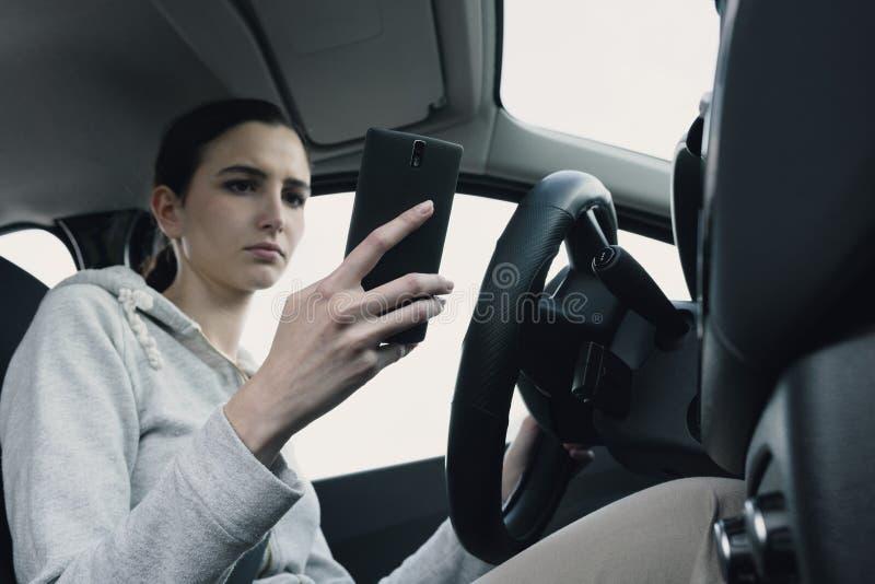 Халатная женщина используя смартфон в ее автомобиле стоковые изображения