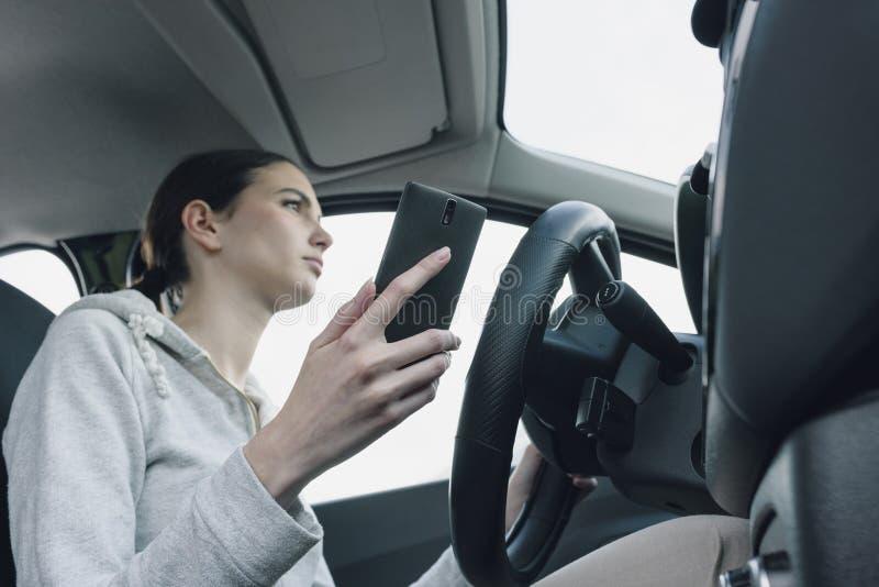 Халатная женщина используя смартфон в ее автомобиле стоковые изображения rf