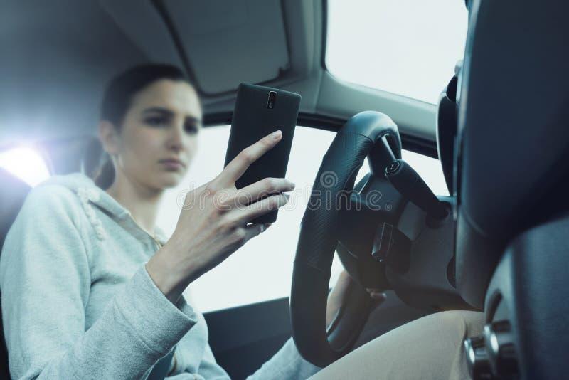 Халатная женщина используя смартфон в ее автомобиле стоковые фотографии rf