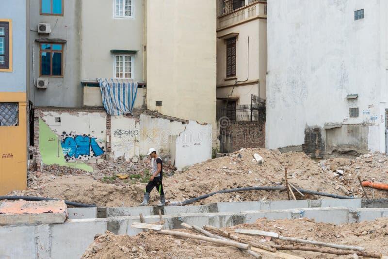 Ханой, Вьетнам - 28-ое апреля 2015: Человек идя на руины сокрушенного дома мимо под сток конструкции городской в улице Xuan Thuy стоковые изображения rf