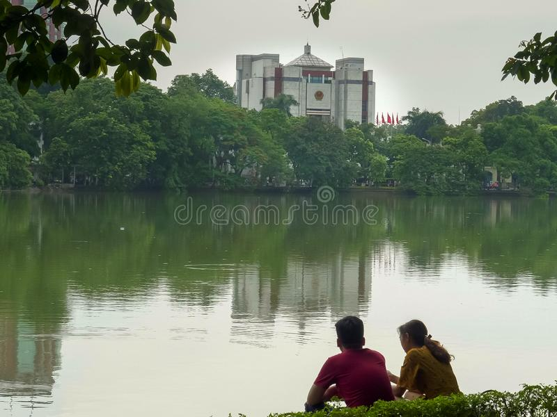 ХАНОЙ, ВЬЕТНАМ - 26-ОЕ ИЮНЯ 2017: молодая пара сидит hoan озером kiem в Ханое стоковое изображение