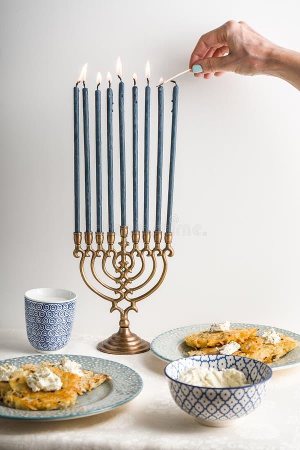 Ханука с освещенными свечами, latkes на плите, сыром творога стоковое фото