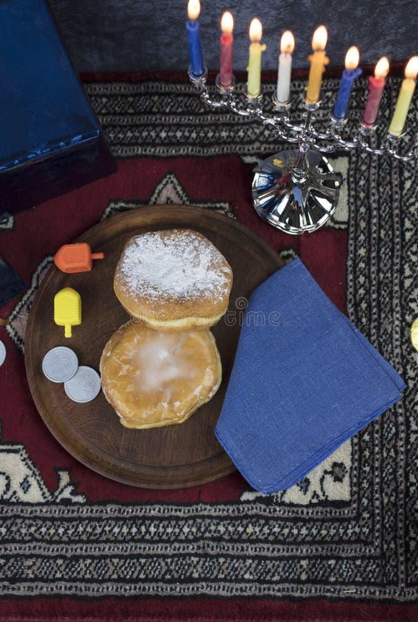 Ханука Menorah с освещенными свечами, подарки, Dreidel и студень заполняют стоковое фото rf