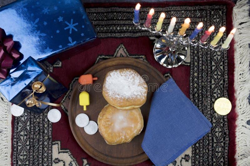 Ханука Menorah с освещенными свечами, подарки, Dreidel и студень заполняют стоковое изображение