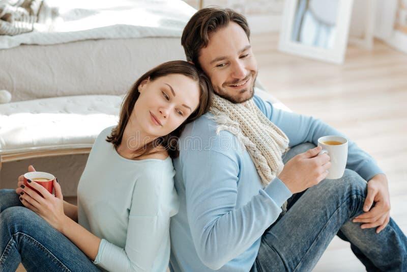 Харизматические молодые пары выпивая горячий чай в спальне стоковое изображение rf