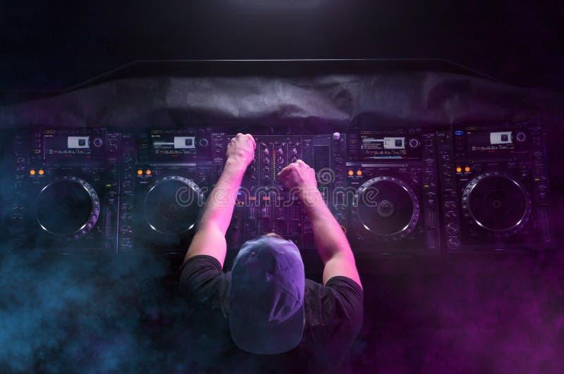 Харизматический диск-жокей на turntable Dj играет на самых лучших, известных чд-плеерах на ночном клубе во время партии EDM, конц стоковые изображения rf