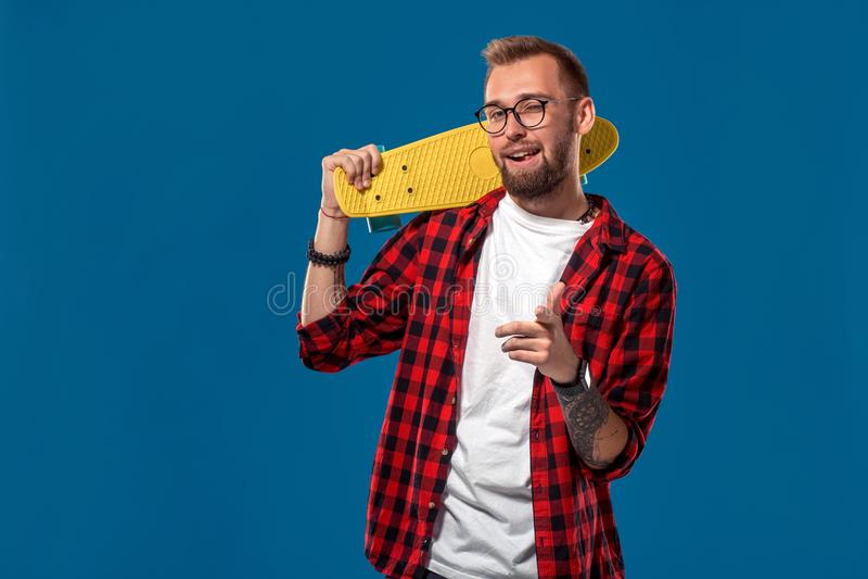 Харизматический жизнерадостный молодой бородатый человек одел в checkered рубашке, белой футболке и стеклах, с желтым скейтбордом стоковые фото