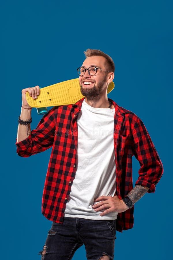 Харизматический жизнерадостный молодой бородатый человек одел в checkered рубашке, белой футболке и стеклах, с желтым скейтбордом стоковая фотография rf