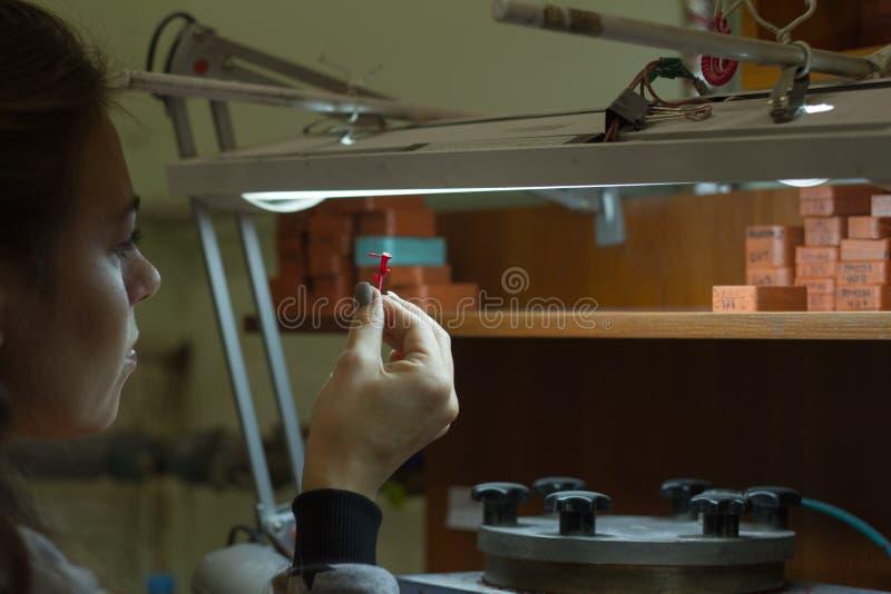 ХАРЬКОВ, УКРАИНА - 31-ое января 2019: Мастерский ювелир держит инструмент работы в его руках и делает украшения на его рабочем ме стоковая фотография