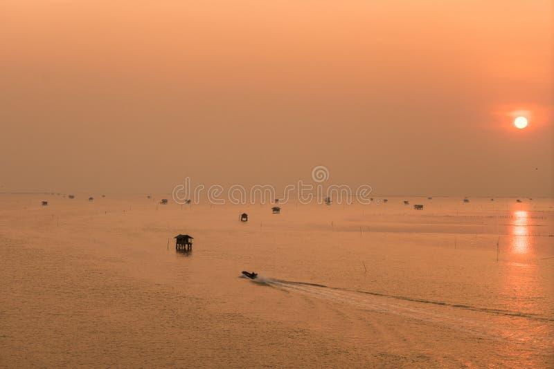 Хата и рыбацкая лодка на море с восходом солнца на Phetchaburi Prov стоковые изображения