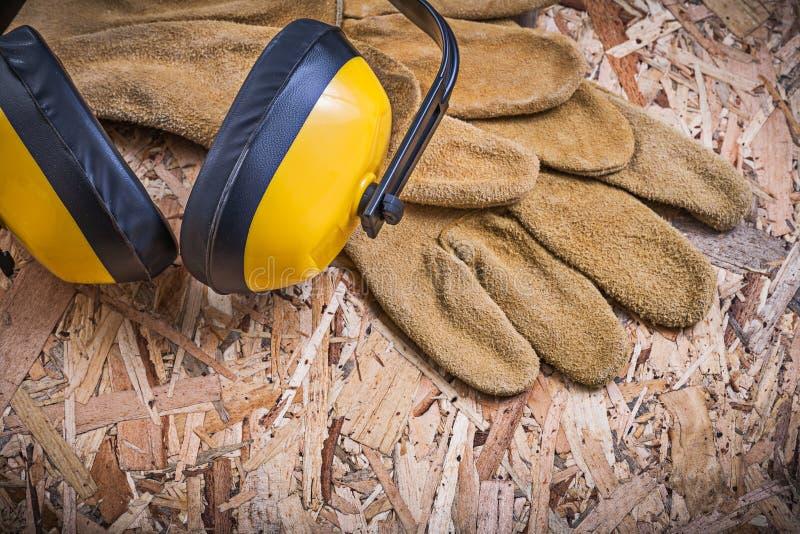 Халявы уха кожаных перчаток безопасности на OSB стоковые изображения