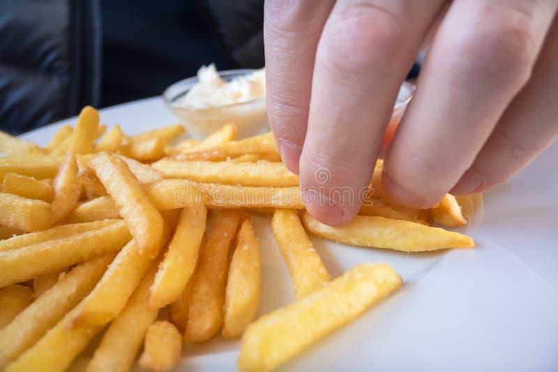 Хватать некоторый французский картофель фри стоковая фотография