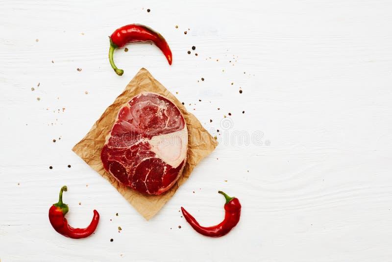 Хвостовик сырого мяса с перцами chili на белизне покрасил деревянный прибой стоковое фото rf