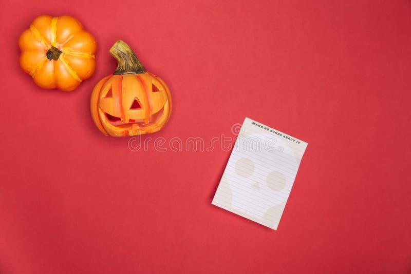 Хеллоуин ваял сторону тыквы смешную и милую вместе с польностью неповрежденной тыквой вдоль бумаги примечаний Красная предпосылка стоковое фото rf