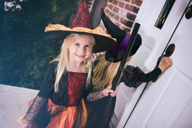 Хеллоуин: Маленькая девочка ждет дверь для того чтобы раскрыть на парадном крыльце стоковая фотография rf