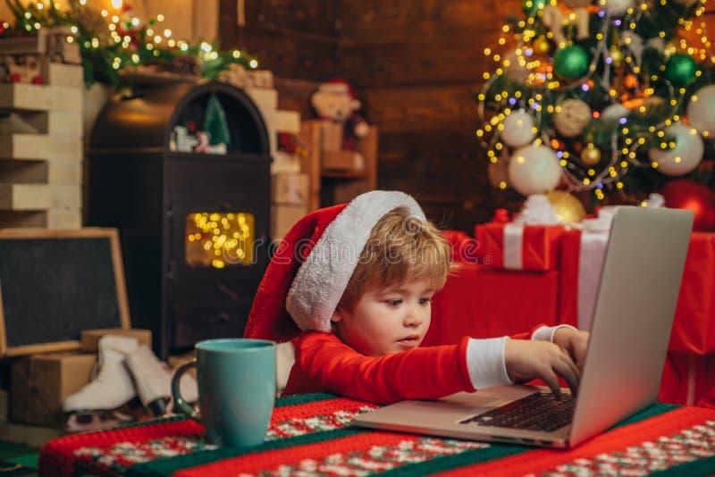 Хелпер Санта маленький Шляпа и костюм santa мальчика имея потеху Ребенок мальчика с ноутбуком около рождественской елки Покупка стоковая фотография rf