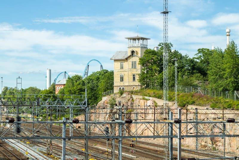 Хельсинки, Финляндия - 12 июня 2019 года: Старая деревянная вилла построена на скале возле железной дороги стоковая фотография