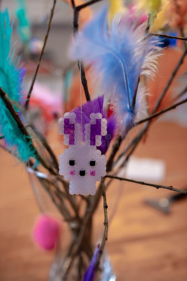 Хельсинки, Финляндия - 25-ое марта 2018: Зайчик пасхи на хворостине пасхи с красочными пер стоковое фото rf