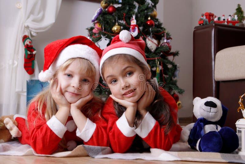 Хелперы Санты девушек лежа под рождественской елкой стоковое изображение