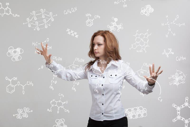 Химик женщины работая с химическими формулами на серой предпосылке стоковая фотография