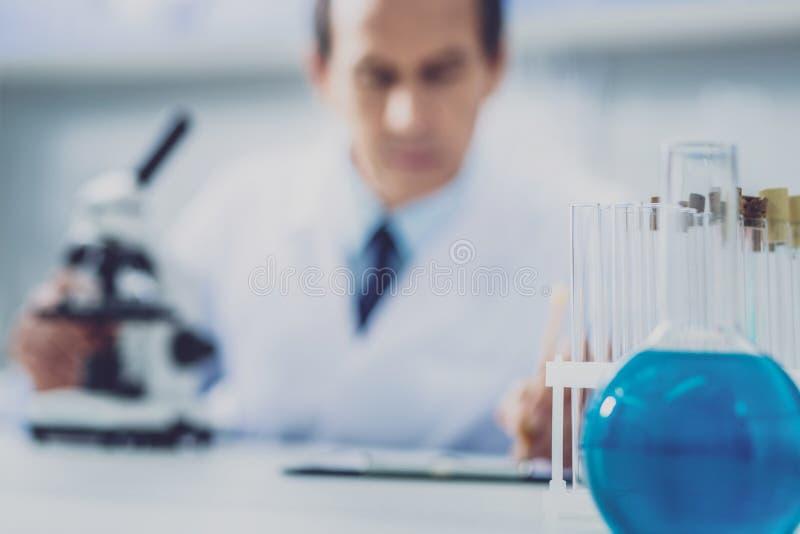 Химик сидя на таблице около шариков с жидкостями стоковые изображения